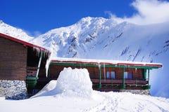 Paisagem bonita com chalé de madeira, o céu azul e a luz do sol no inverno Montanhas de Fagaras Foto de Stock Royalty Free