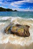Paisagem bonita da costa de mar com ondas e pedra Ilha verde no fundo Pedra grande na água Oceano com obscuridade - s azul Fotos de Stock