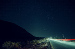 A paisagem bonita da noite das estrelas na silhueta do céu e da montanha perto da estrada com carro arrasta Estrada nas montanhas fotografia de stock