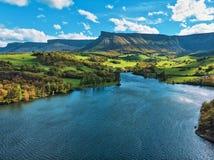 Paisagem bonita do lago, de campos verdes e de montanhas imagem de stock