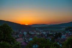 Paisagem bonita do nascer do sol sobre a cidade pequena em montanhas da floresta Romênia, Sighisoara - 2016 Imagens de Stock