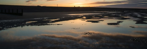 A paisagem bonita do panorama do nascer do sol refletiu nas associações na praia Imagem de Stock