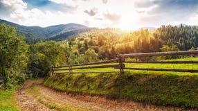 Paisagem bonita do verão com cerca e as montanhas de madeira azul Imagem de Stock Royalty Free