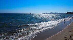 Paisagem cênico com céu azul e as nuvens brancas entre a água e as montanhas do oceano Foto de Stock
