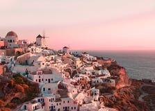 Paisagem clássica bonita com construções e os moinhos de vento brancos do vintage em Oia na ilha de Santorini, Grécia no por do s Imagens de Stock Royalty Free