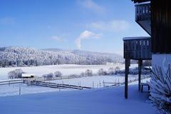 Paisagem coberto de neve do inverno com parte do balcão, as montanhas e as florestas e os campos na neve imagens de stock