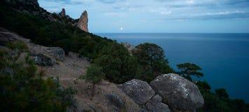 Paisagem colorida da noite com o trajeto e as rochas lunares da Lua cheia no verão Paisagem da montanha no mar Imagem de Stock