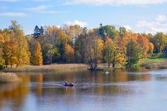 Paisagem colorida do outono com barco do vrssel e as folhas de queda Dia de outubro no parque de Pavlovsk, StPetersburg, Rússia Fotografia de Stock Royalty Free