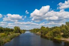 Paisagem com as nuvens brancas acima do rio Imagem de Stock