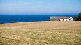 Paisagem com campo, casa e mar Imagem de Stock Royalty Free