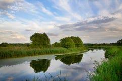A paisagem com curvatura do rio e as nuvens refletiram na água fotografia de stock
