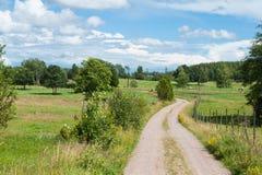 Paisagem com a estrada de terra na Suécia rural Foto de Stock