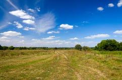 Paisagem com a estrada de terra no campo imagens de stock royalty free