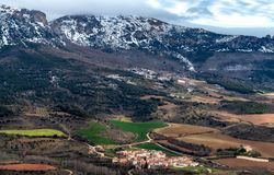 Paisagem com montanhas nevados, campos de exploração agrícola e vila no nascer do sol imagens de stock