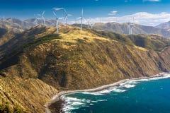 Paisagem com montes, oceano e turbinas eólicas Foto de Stock