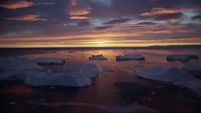 Paisagem com os iceberg no icefjord de Gronelândia com nascer do sol do por do sol do sol da meia-noite no horizonte Metragem aér filme
