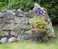 Paisagem com pansies em um grande potenciômetro e em uma bicicleta decorativa foto de stock