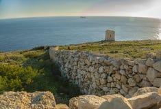 Paisagem com a parede da pedra calcária e a torre tipic de Tal Hamrija foto de stock