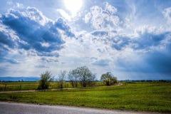 Paisagem com por do sol e nuvens Imagem de Stock
