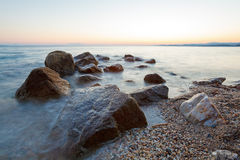 Paisagem com rochas e ondas no por do sol Imagens de Stock Royalty Free
