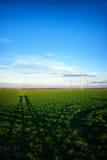 Paisagem com turbinas eólicas e sombras dos povos Imagem de Stock