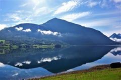 Paisagem com uma montanha do bBlue que towerning sobre a água imóvel com uma reflexão imagem de stock