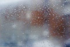 A paisagem da cidade é mal distinguível através de uma janela enlameada com gotas da chuva imagem de stock