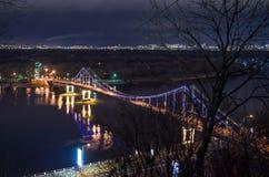 Paisagem da cidade da noite com o passadiço sobre o rio Dniper e lanternas de incandescência bonitas imagens de stock royalty free