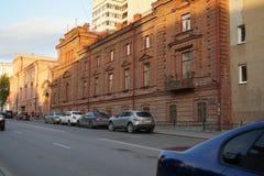 Paisagem da cidade: Rua de 22 Pervomaiskaya, a construção do tijolo vermelho no por do sol Escola de m?sica imagens de stock