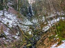 Paisagem da floresta com uma cachoeira congelada com sincelos e um bocado de fluir a água em Wasserfall Alemanha foto de stock
