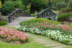 Paisagem da jardinagem floral com caminho e ponte Fotografia de Stock