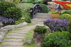 Paisagem da jardinagem floral com caminho e ponte Imagens de Stock
