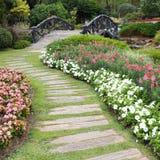 Paisagem da jardinagem floral com caminho e ponte Fotografia de Stock Royalty Free
