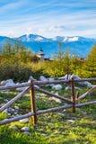 Paisagem da mola com cerca de madeira, árvores, picos de montanha nevado Imagem de Stock Royalty Free