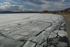 Paisagem da mola com tração do gelo no lago e os ciclistas e os povos que montam ao longo dele imagem de stock royalty free