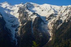 A paisagem da montanha com floresta colorida e elevação neve-tampou picos do dia surpreendente bonito das montanhas de Cáucaso Fotografia de Stock Royalty Free
