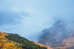 Paisagem da montanha com névoa abaixo dos picos imagem de stock