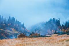 Paisagem da montanha com névoa abaixo dos picos e das nuvens acima deles fotografia de stock