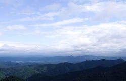 Paisagem da montanha, com os picos de montanha cobertos com a floresta e um céu nebuloso Imagem de Stock