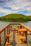Paisagem da montanha com a plataforma de madeira com as cadeiras e as tabelas sobre o lago Gozna cercadas pela floresta Fotografia de Stock Royalty Free