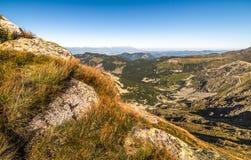 Paisagem da montanha com rochas e grama no primeiro plano Imagem de Stock