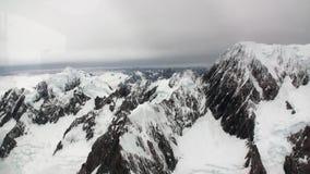 Paisagem da montanha da neve e da opinião branca das nuvens do helicóptero em Nova Zelândia filme