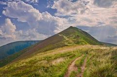 Paisagem da montanha do verão com um trajeto aos wi da montanha e do céu Fotografia de Stock