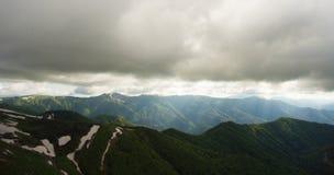 Paisagem da montanha Os raios claros perfuram a maneira com o lo sombrio Fotografia de Stock Royalty Free