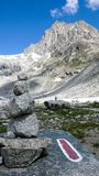A paisagem da montanha rochosa com picos de montanha e monte de pedras e vermelho e o branco arrastam o marcador Foto de Stock
