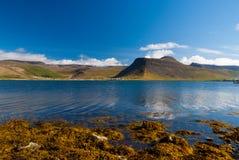 Paisagem da montanha vista do mar no isafjordur, Islândia Litoral montanhoso no céu azul ensolarado Férias de verão sobre imagem de stock