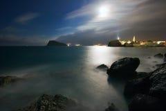 Paisagem da noite com o mar, a lua e as rochas Fotografia de Stock