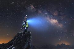 Paisagem da noite Um esquiador backcountry profissional com uma trouxa e os esquis está em uma rocha nas montanhas e brilha imagem de stock royalty free