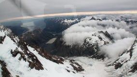Paisagem da opinião do panorama da montanha da neve da janela do helicóptero em Nova Zelândia vídeos de arquivo