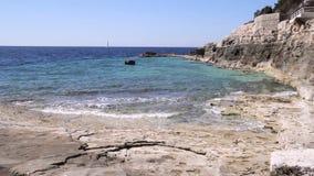 Paisagem da praia com as ondas que deixam de funcionar na rocha coral em Istria, Croácia Ondas que quebram na praia rochoso, form vídeos de arquivo